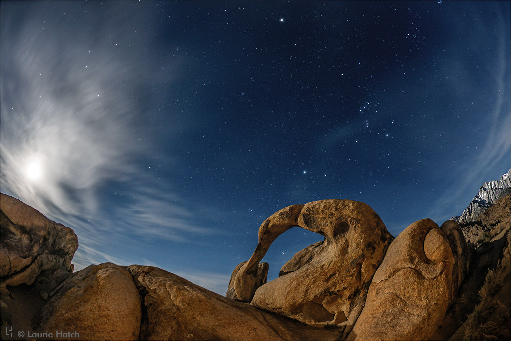 The waning gibbous moon (95% illumination, 2 days past full) is diffused by thin clouds as it rises over the Alabama Hills and the famed Möbius Arch.